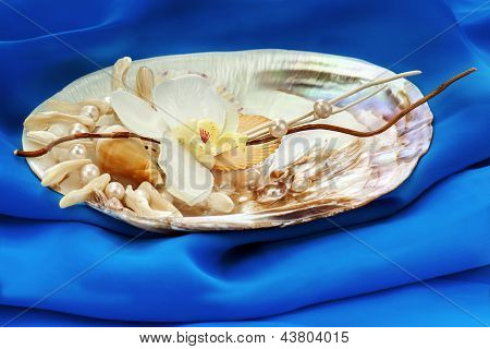Composition From Pearls, Coral And Orchids On Blue Background.