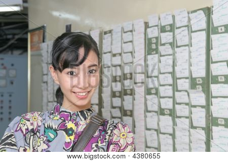 Female Worker At Absent Punch Card Smiling