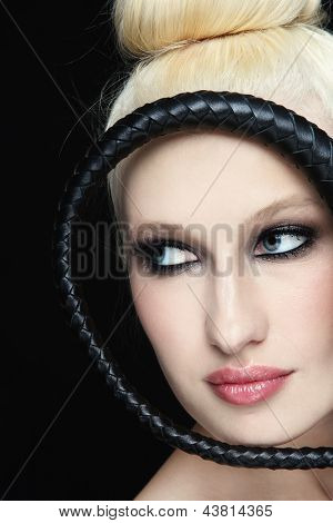 Close-up portrait of young beautiful blond woman with braided bull whip