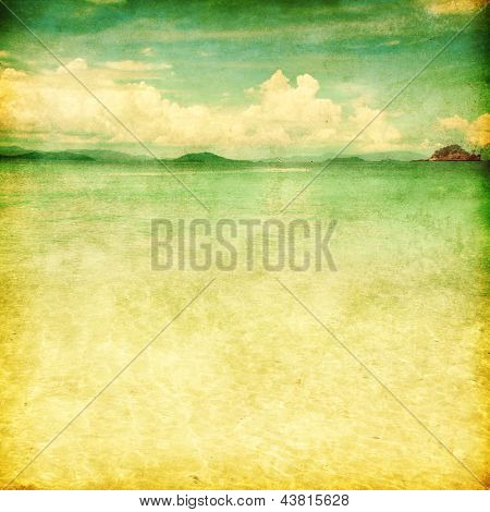Grunge photo of sandy beach over blue sky.