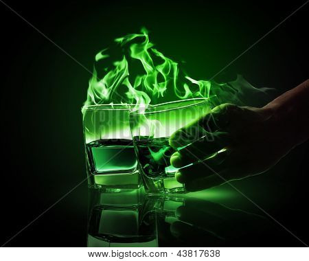 Hand holding one of two glasses of burning green absinth