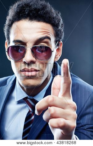 Vertical portrait of a cool businessman wagging his finger
