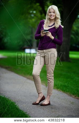 Portrait of attractive young smiling woman using cell phone in park