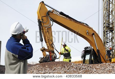 bulldozer and industrial workers in action, inside building site