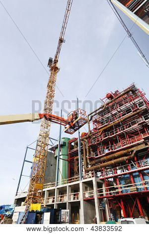 worker being hoisted by hydraulic platform inside construction plant