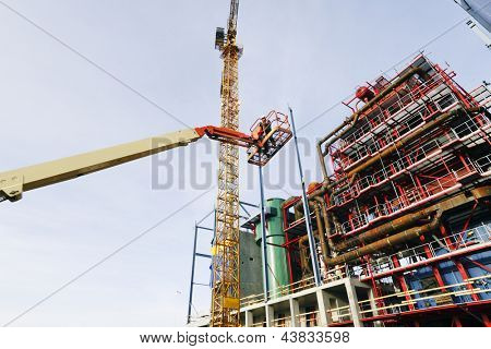 hydraulic platform hoisting site-worker in the air, factory construction plant