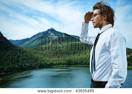 Successful business man standing on a peak of the mountain and purposefully looking away.