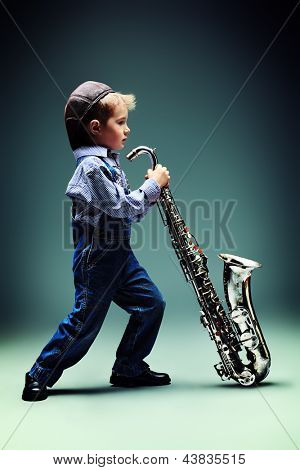 Portrait of a cute little boy jazzman playing his saxophone. Retro style.