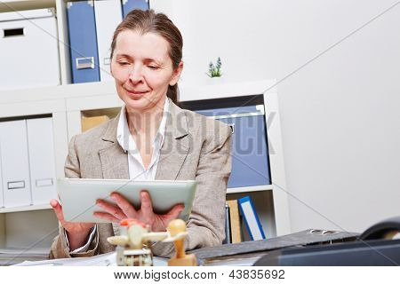 Elderly business woman working with tablet PC in her office at the desk
