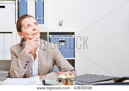 Pensive business woman sitting in her office at the desk