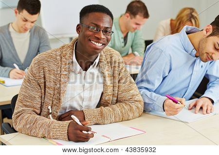 Happy smiling african student taking notes in university class