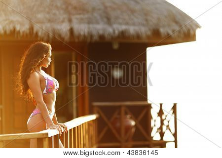 Woman standing near fence of tropical hotel