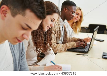Many students learning with laptop computer in lecture of university