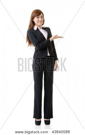 Attractive business woman showing and introducing, full length portrait isolated on white background.
