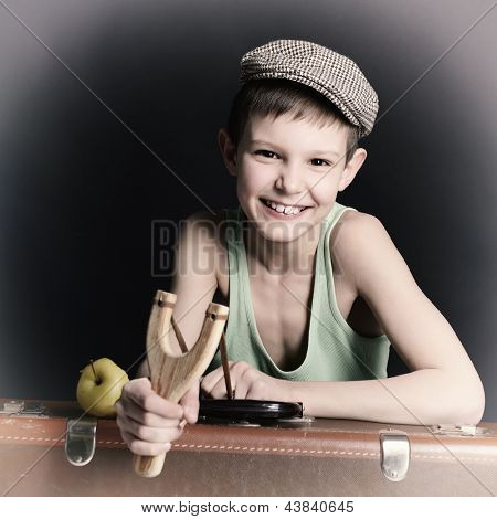 vintage art portrait of little boy looking at camera holding catapult and  leaning on old suitcase, retro stylization of 30-50s, toned