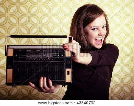 art portrait of young smiling ecstatic woman holding radio player in room with vintage wallpaper, retro stylization 60-70s, toned