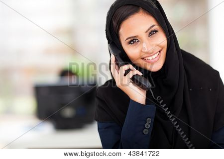 young happy Muslim businesswoman talking on landline phone