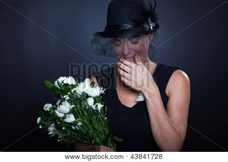 sad widow with mourning clothing and flowers crying at husband's funeral