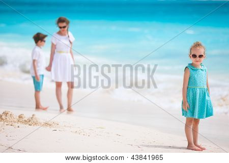 Adorable little girl and her family at tropical beach