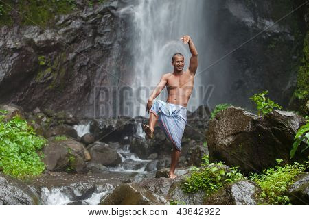 Young handsome man enjoying waterfall in the tropics