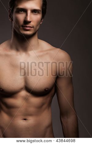 Handsome young man with naked torso on a grey background
