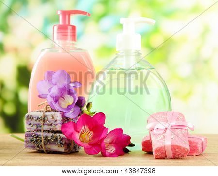 Liquid and hand-made soaps on wooden table, on green background