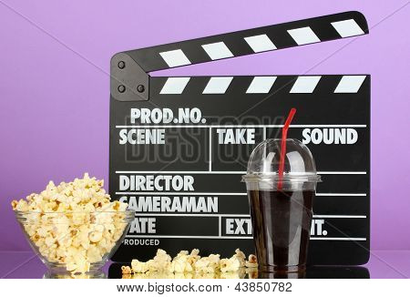 Movie clapperboard, cola and popcorn on purple background