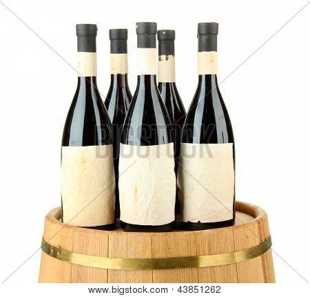 Wine bottles on wooden barrel, isolated on white