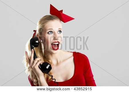 Beautiful fashion woman with a astonished expresion and holding a  vintage phone