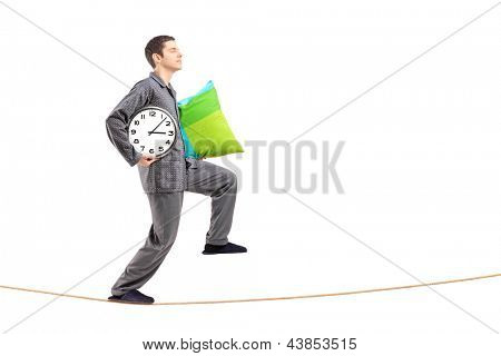 Full length portrait of a young man with a pillow and clock sleepwalking on a rope isolated against white background