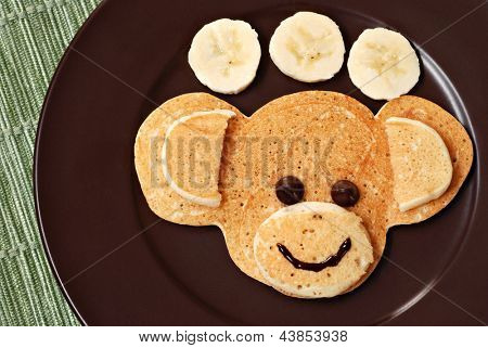 Fun kid's breakfast of a smiling monkey face with chocolate chips for eyes on plate with banana slices.