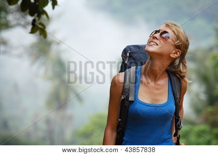 Young tourist with backpack walking in tropical forest