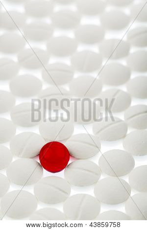 white tablets in contrast with a red tablet, symbol photo bullying and individuality
