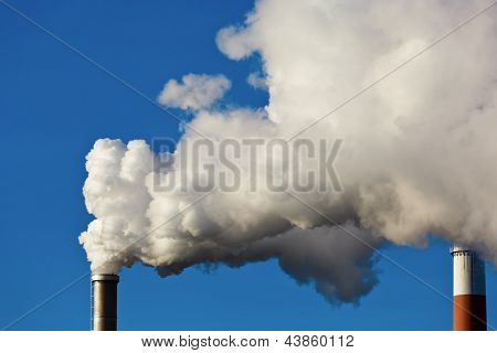 the smoking chimneys of a factory against a blue sky. smoke rises from chimneys white