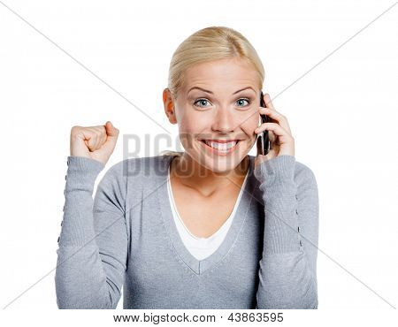 Smiley girl speaking on phone with her fist up, isolated on white