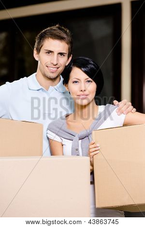 Happy couple carrying pasteboard packages while moving to new house