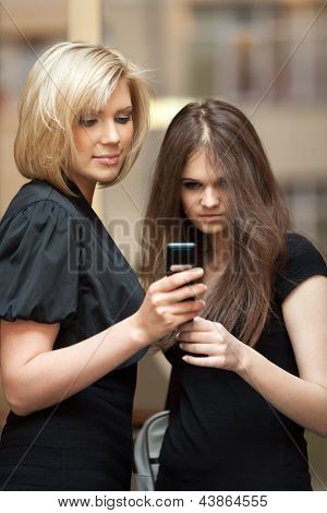 Two young women looking at mobile phone against office window