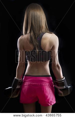 Beautiful woman kick boxing over dark background