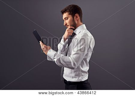 sideview portrait of thoughtful businessman with tablet pc. studio shot over dark background