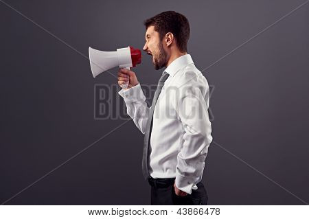 sideview portrait of businessman with megaphone over dark background