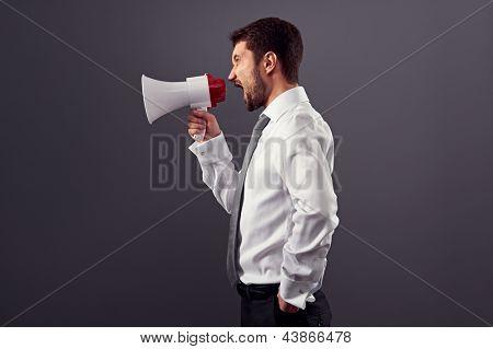 Retrato de la vista lateral del empresario con megáfono sobre fondo oscuro
