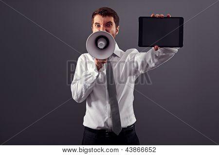empresário emocional mostrando a tela do tablet pc e gritando com megafone contra backg cinza