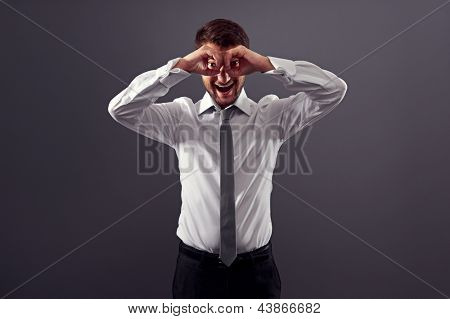 excited businessman looking through imaginary binocular. studio shot over dark background