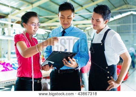 Shift supervisor or foreman, together with the owner or CEO and the designer, look at a draft for the new collection, they standing in a textile factory