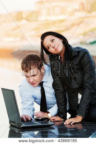 Young business couple using laptop
