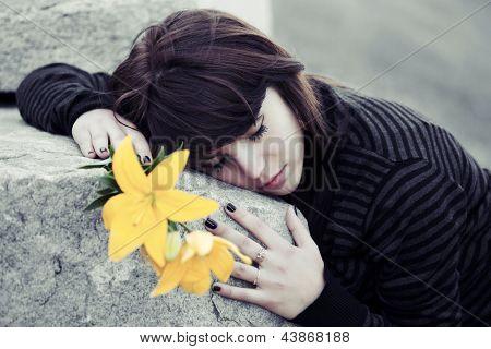 Sad young woman lying on the stone