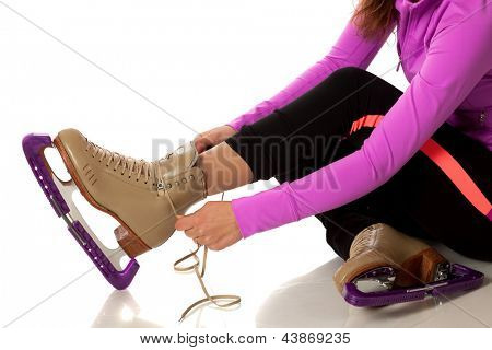 Figure skater tying skates. Studio shot over white.
