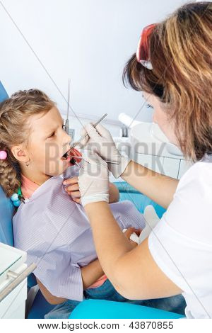 Dentist examining an unhappy child's teeth