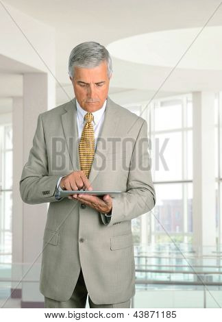 Middle aged businessman looking at his tablet computer while standing in a modern office building.