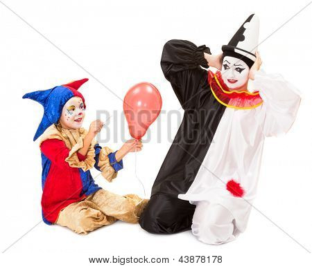 Little clown girl scaring a pierrot by making a balloon explode